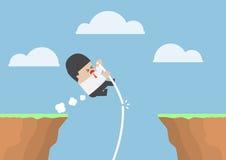 O salto com vara do homem de negócios através do penhasco mas falha Foto de Stock Royalty Free