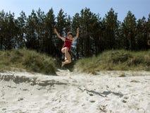 O salto do menino da duna Fotos de Stock Royalty Free