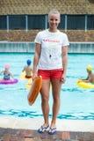 O salvamento fêmea da terra arrendada da salva-vidas pode na piscina Fotografia de Stock Royalty Free