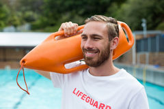 O salvamento levando da salva-vidas masculina pode na piscina Fotografia de Stock