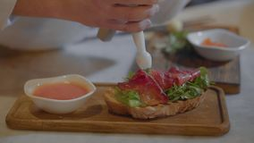 O sanduíche com rúcula e os salmões salgados está cozinhando no fim do restaurante acima Mãos do cozinheiro chefe que fazem o ali video estoque