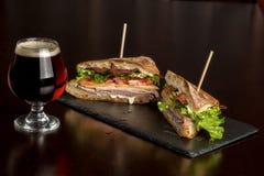 O sanduíche de clube cortou ao meio com um vidro gelado da cerveja Imagem de Stock