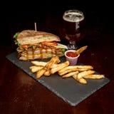 O sanduíche de clube famoso do monstro com fritadas e uma cerveja Fotografia de Stock