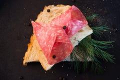 O sanduíche do salame serviu com aneto e pimenta preta fotografia de stock royalty free