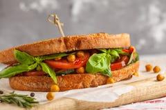O sanduíche do vegetariano com tomate, pepino, fritou grãos-de-bico e b Foto de Stock