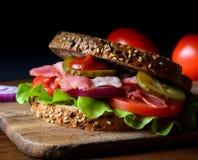 O sanduíche preparou-se recentemente com bacon, tomate, pepino, cebola no brinde inteiro do trigo da grão Imagem de Stock Royalty Free