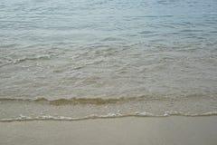 O Sandy Beach limpo pastel macio com água do mar clara fresca e a onda espumosa branca morna alinham o fundo e o copyspace na cos Imagens de Stock