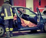 O sapador-bombeiro controla a pessoa envolvida em um carro trágico acciden Imagem de Stock Royalty Free