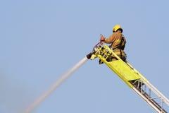 O sapador-bombeiro extingue o incêndio Fotografia de Stock
