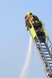 O sapador-bombeiro extingue o incêndio Foto de Stock Royalty Free