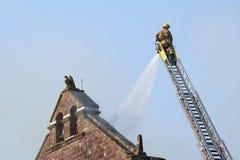 O sapador-bombeiro extingue o incêndio Fotografia de Stock Royalty Free
