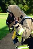 O sapador-bombeiro prepara seu instrumento de respiração na cena do fogo Fotografia de Stock Royalty Free