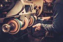 O sapateiro executa sapatas na máquina do moedor do ofício do estúdio imagens de stock