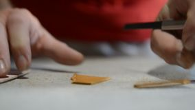 O sapateiro faz o teste padrão no papel e corta o couro video estoque