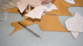 O sapateiro faz o teste padrão no papel e corta o couro filme