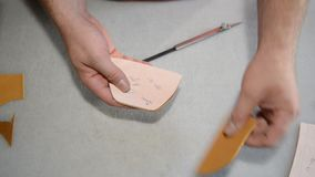 O sapateiro faz o teste padrão no papel e corta o couro vídeos de arquivo