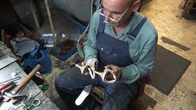 O sapateiro no trabalho O processo de reparar sapatas na oficina video estoque