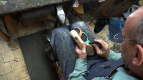O sapateiro no trabalho O processo de reparar sapatas na oficina filme