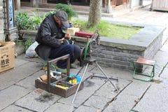 O sapateiro repara sapatas na cidade Wuzhen da água, China Imagens de Stock