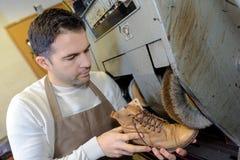 O sapateiro repara sapatas na máquina do moedor do ofício do estúdio fotografia de stock