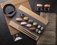 O sashimi do sushi e os rolos de sushi ajustados serviram na ardósia de pedra Imagem de Stock Royalty Free