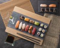 O sashimi do sushi e os rolos de sushi ajustados serviram na ardósia de pedra Fotografia de Stock Royalty Free