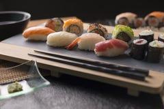 O sashimi do sushi e os rolos de sushi ajustados serviram na ardósia de pedra Fotos de Stock Royalty Free