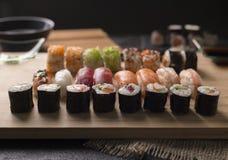 O sashimi do sushi e os rolos de sushi ajustados serviram na ardósia de pedra Imagens de Stock Royalty Free