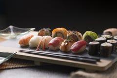 O sashimi do sushi e os rolos de sushi ajustados serviram na ardósia de pedra Fotos de Stock