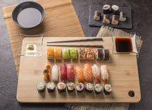 O sashimi do sushi e os rolos de sushi ajustados serviram na ardósia de pedra Foto de Stock Royalty Free