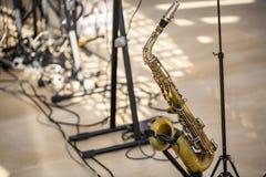 O saxofone da cor dourada está na cremalheira na fase imagem de stock