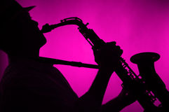 O saxofone jogou no fundo da cor-de-rosa da silhueta Imagens de Stock Royalty Free