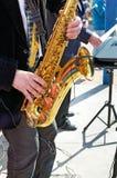 O saxofone nas mãos do músico Imagens de Stock