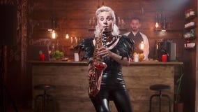 O saxofonista fêmea bonito com brilhante compõe executa em um café do jazz video estoque