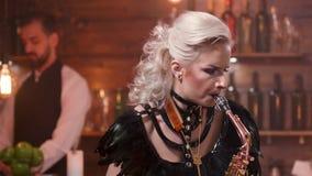 O saxofonista fêmea bonito com brilhante compõe executa em um restaurante filme