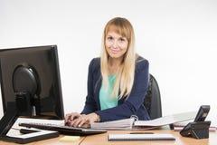 O secretário que trabalha no computador, fim o dobrador com os originais é Imagens de Stock