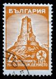 O selo impresso em Bulgária mostra o monumento de Shipka fotos de stock