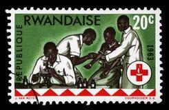 O selo impresso em Ruanda é dedicado ao 100th aniversário da cruz vermelha internacional Fotos de Stock Royalty Free