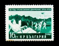 O selo postal de Bulgária mostra o homem na cadeira, jogadores de voleibol, sindicatos 50 anos de aniversário, cerca de 1954 Fotos de Stock