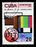 O selo postal de Cuba mostra o aparelho de televisão, o rádio, o globo e o emblema, ano de uma comunicação, cerca de 1983 Fotografia de Stock Royalty Free