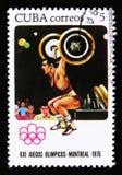 O selo postal de Cuba mostra o levantamento de peso, série devotada aos jogos de Montreal 1976, cerca de 1976 Fotos de Stock
