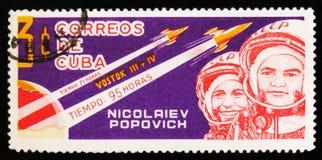 O selo postal de Cuba mostra retratos de Nikolayev e de Popovich, cosmonautas soviéticos, com foguete Vostok 3 e 4, cerca de 1963 Foto de Stock Royalty Free