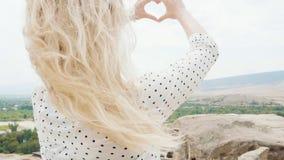 O sentimento da alegria, a felicidade e a admiração, jovem mulher com mãos femininos macias mostra a forma do coração usando suas video estoque