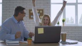 O sentimento feliz do homem de negócios excitado olhando a tela do portátil que senta-se no local de trabalho, comemora o sucesso video estoque