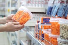 O ser humano escolhe plástico ondulado obstrui na loja de bens da construção foto de stock