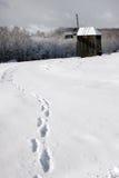 O ser humano segue na neve que conduz ao moinho velho Foto de Stock