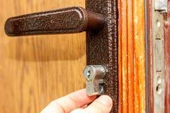 O serralheiro instala a fechadura da porta nova na porta de madeira fotos de stock royalty free
