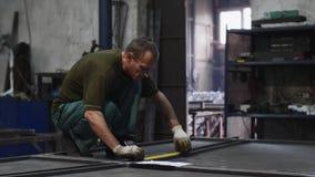 O serralheiro mede a fita métrica do comprimento de barras de metal e faz marcas na oficina vídeos de arquivo