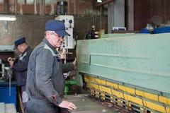 O serralheiro trabalha em tesouras mecânicas da guilhotina Foto de Stock