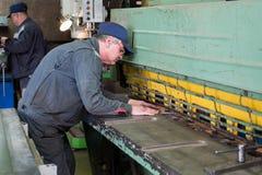 O serralheiro trabalha em tesouras mecânicas da guilhotina Foto de Stock Royalty Free